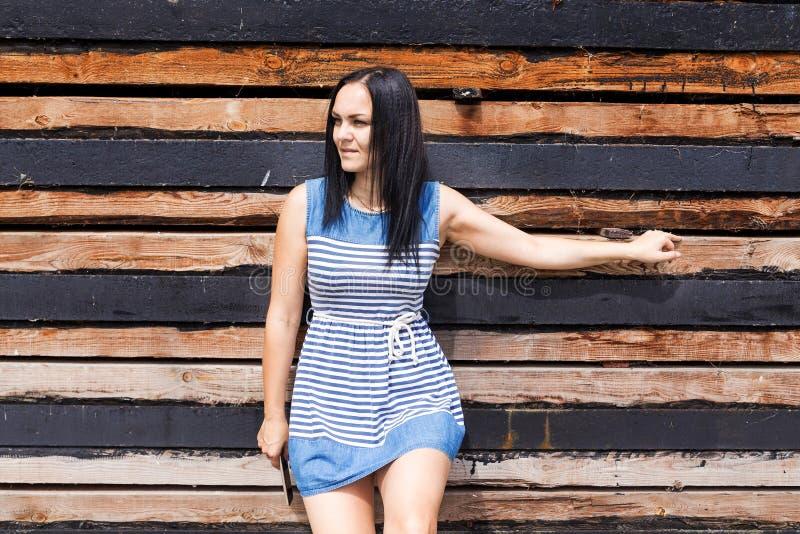 Dorosła dziewczyna w pasiastej sukni na drewnianym tle obraz stock