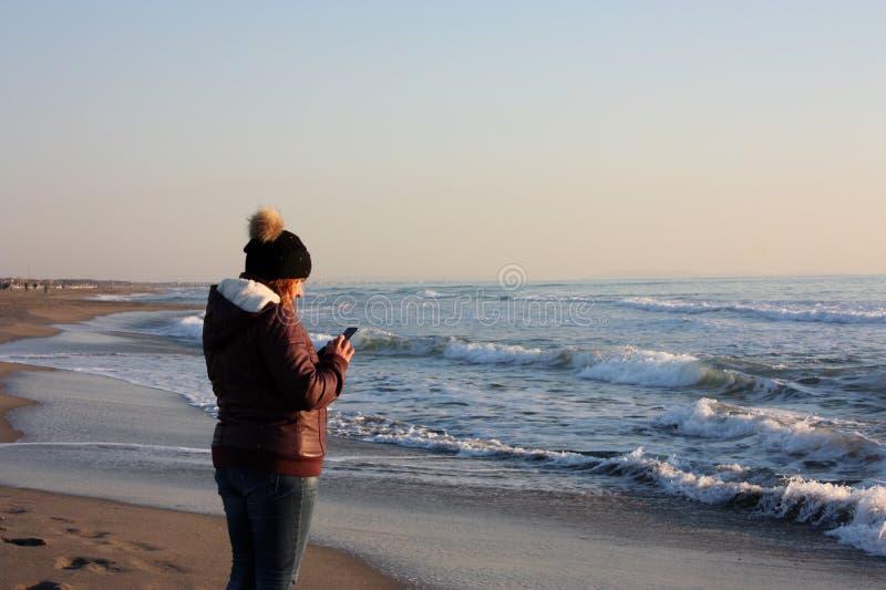Dorosła kobieta chodzi morzem na linii brzegowej, sprawdza jej telefon komórkowego obraz royalty free