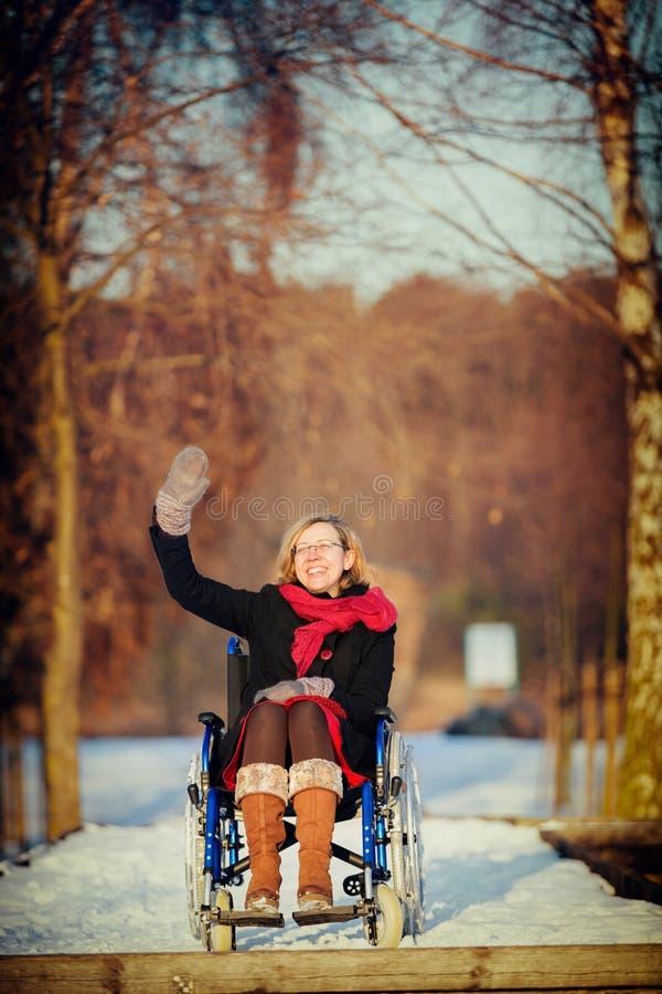 Dorosła kobieta na wózka inwalidzkiego falowaniu obrazy royalty free