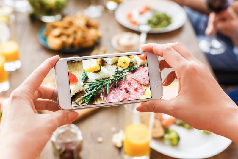 Dorosła kobieta robiąca zdjęcie jedzenia na smartfonie zdjęcia stock