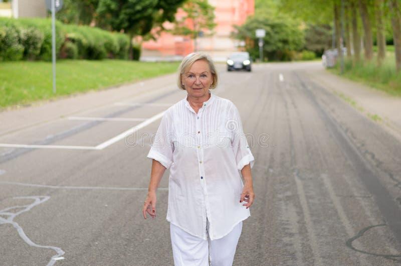 Dorosła kobieta w Wszystkie Białym odprowadzeniu przy ulicą obraz stock