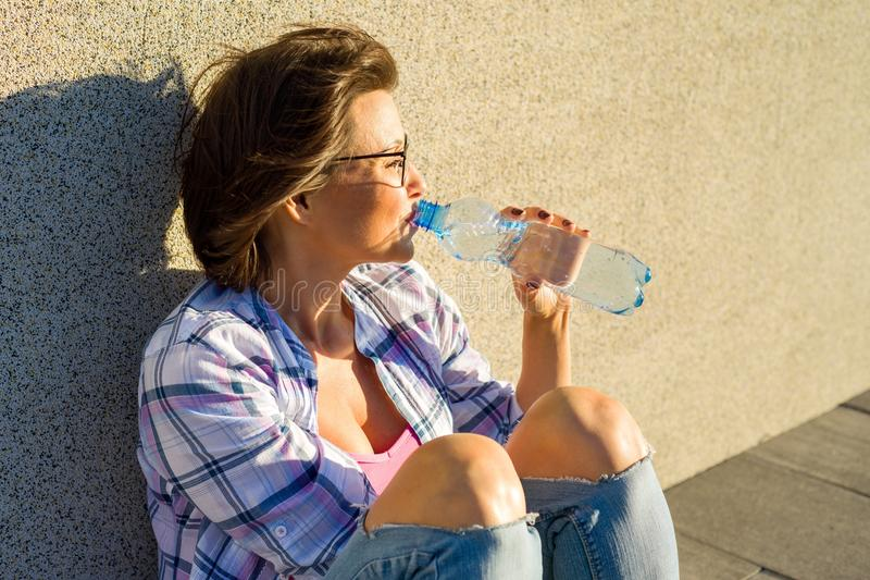 Dorosła kobieta z szkłami jest wodą pitną od butelki na gorącym letnim dniu fotografia stock