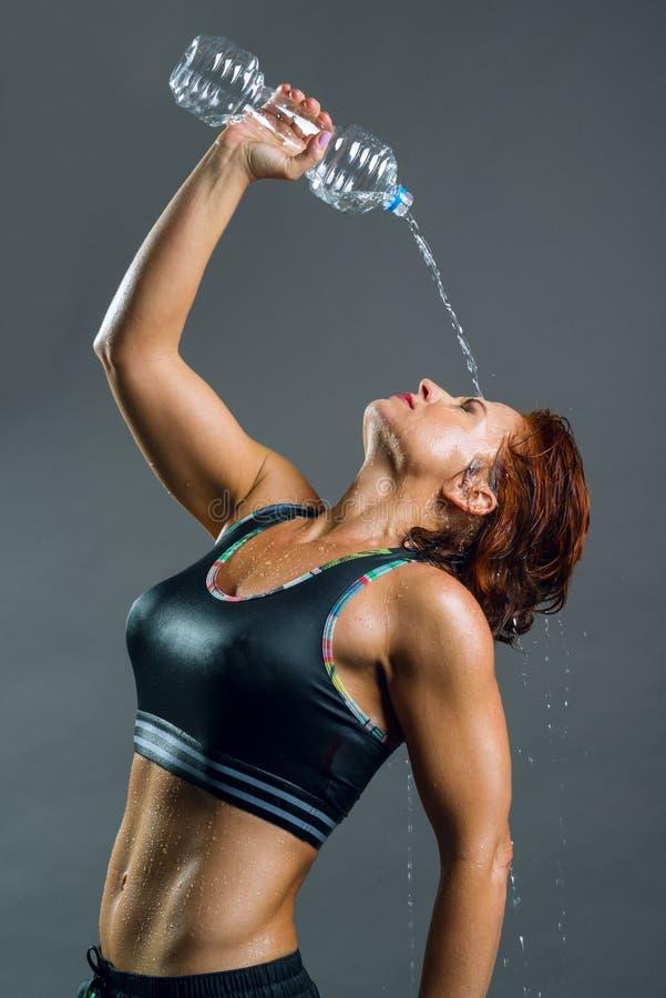 Dorosła mięśniowa sportowa sprawności fizycznej kobieta w sportów ubraniach nalewa wodę od butelki po trenować Szary tło, miedzia obrazy stock