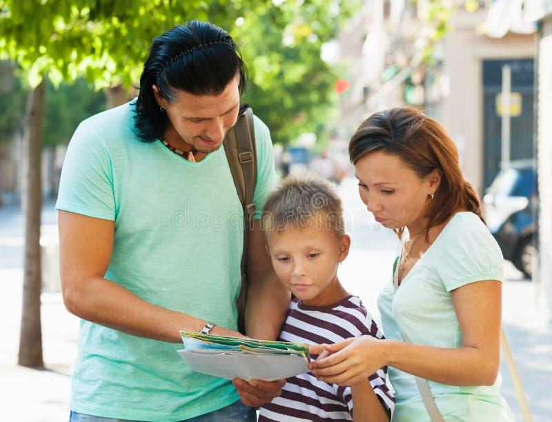 Dorosła para z nastolatkiem patrzeje mapę zdjęcia stock