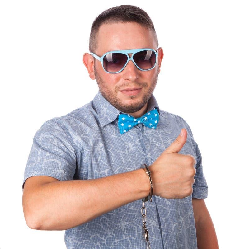 Dorosła samiec z brodą w błękitnym łęku krawacie w lato koszula w policja kajdankach pokazuje że jest świetnie zdjęcia stock