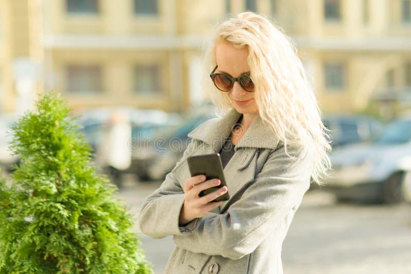 Dorosła uśmiechnięta blondynki kobieta opowiada na telefonie komórkowym, miasta uliczny tło, jesień słoneczny dzień zdjęcia stock