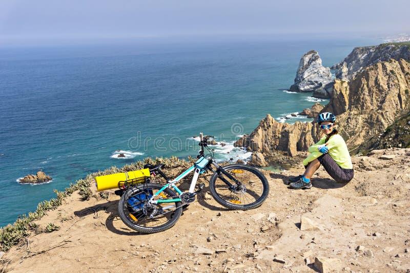 Dorosłe atrakcyjne żeńskie cyklista pozy na oceanu skalistym wybrzeżu fotografia royalty free