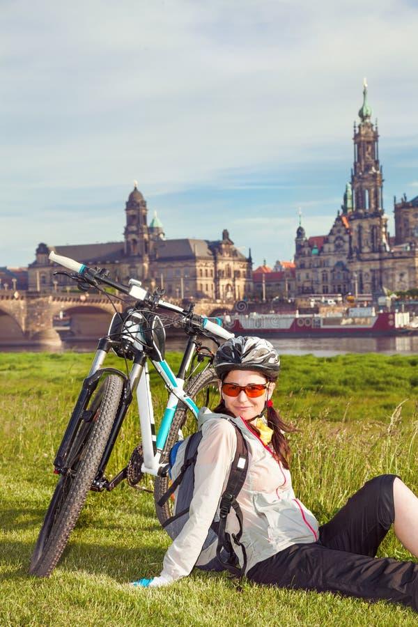 Dorosłego atrakcyjnego żeńskiego cyklisty siedzący obsiadanie na trawie i obrazy royalty free