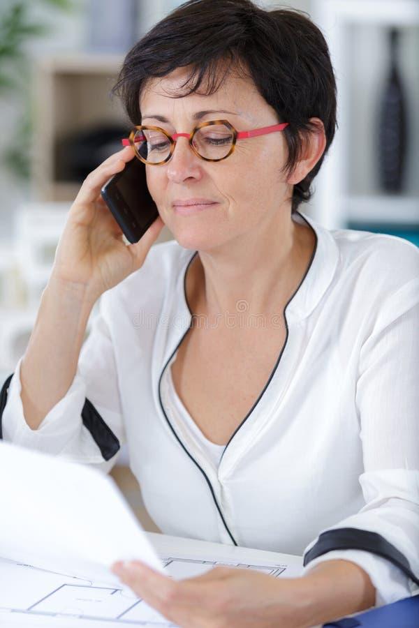 Dorosłej kobiety architekt opowiada telefon w hełmie z papierowymi dokumentami obraz stock