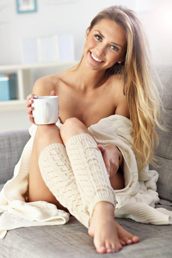 Dorosłej kobiety obsiadanie na kanapie z kawą fotografia stock