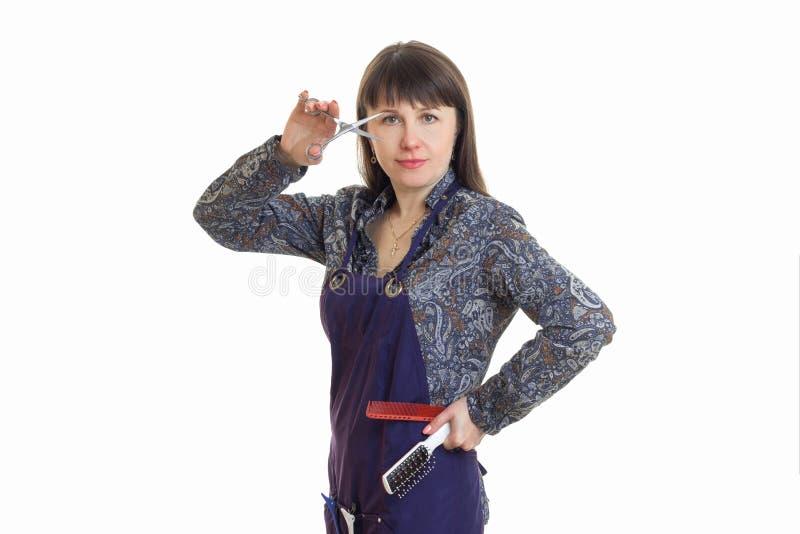 Dorosłej kobiety stylista z narzędziami w rękach jest ubranym fartucha obraz stock
