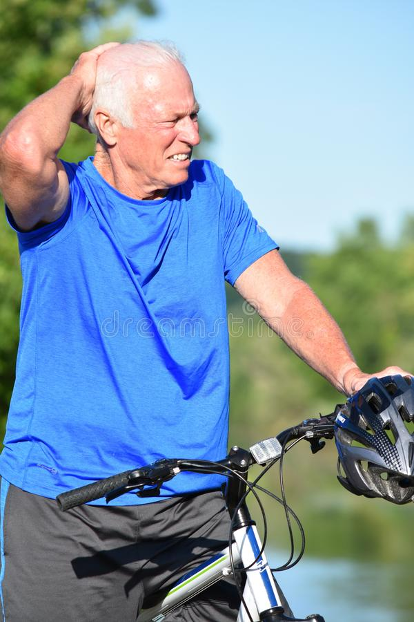 Dorosłej samiec atleta Odpoczywa Będący ubranym hełm jazdy rower zdjęcie stock