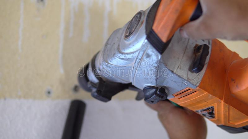 Dorosłej samiec budowniczy robi dziury na ścianie z świderem podczas lotniczego conditioner obraz royalty free