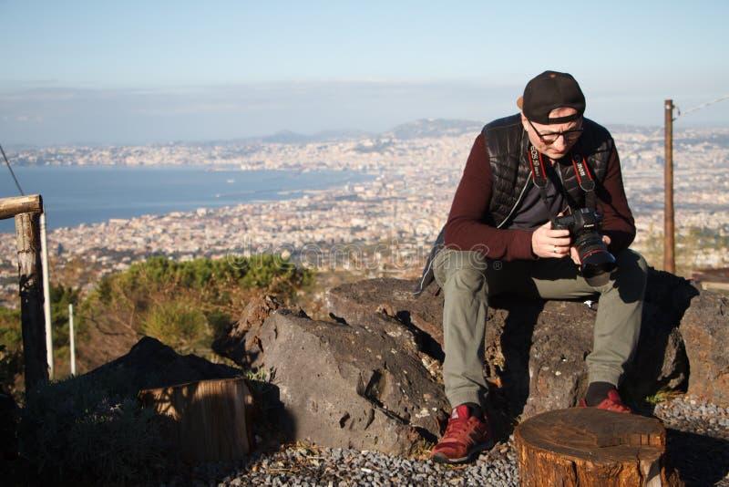 Dorosłej samiec fotograf z kamerą w jego wręcza obsiadanie na górze góry Vesuvius na tle Naples w Włochy fotografia royalty free