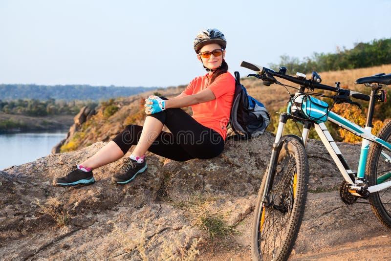Dorosły atrakcyjny żeński cyklista jest odpoczynkowy fotografia royalty free