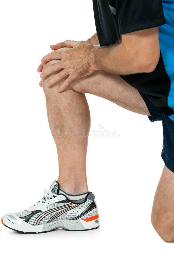 Dorosły atrakcyjny mężczyzna w sportswear kolana bólu urazu obolałości odizolowywającej obrazy royalty free