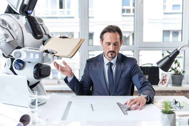 Dorosły biznesmen w kostiumu trudzi się z koncentracją zdjęcia stock