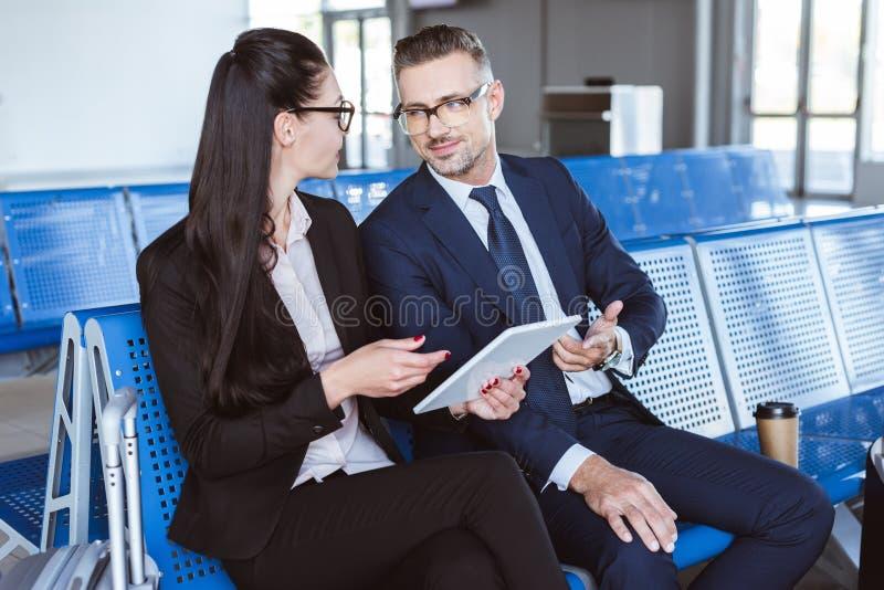 dorosły biznesmena i bizneswomanu obsiadanie przy wyjściowym holem w lotnisku i obraz royalty free