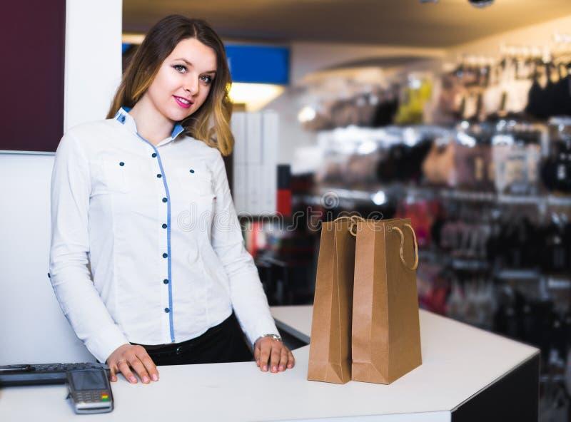 Dorosły dziewczyna sprzedawca wystawia różnorodnych zakupy zdjęcia stock