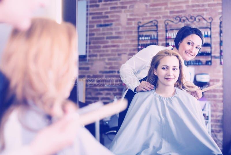 Dorosły fryzjer słucha życzenia młoda kobieta fotografia stock