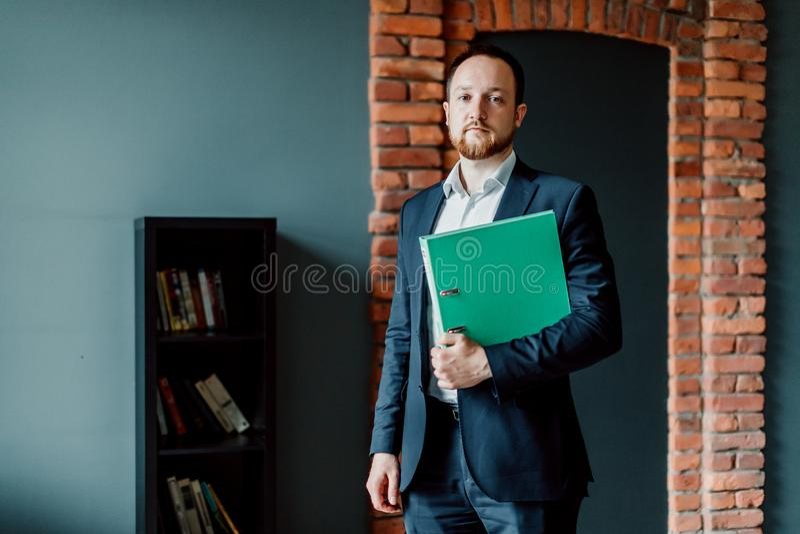 Dorosły i pomyślny księgowy w kostiumu jest stojący zieloną falcówkę z raportami w jego rękach i trzymający fotografia royalty free