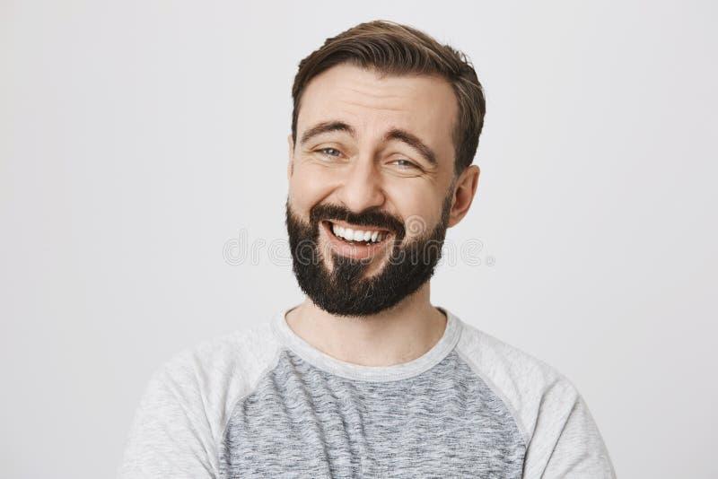 Dorosły mężczyzna śmia się z brodą i wąs patrzejący kamerę nad białym tłem Przystojna brunetka ogląda zdjęcie royalty free
