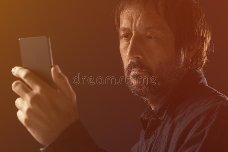 Dorosły mężczyzna patrzeje telefonu komórkowego ekran zdjęcia royalty free