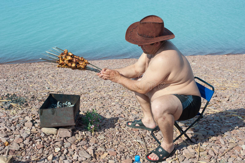 Dorosły mężczyzna przygotowywa smażącego mięso Na jeziorze odpoczynek fotografia royalty free