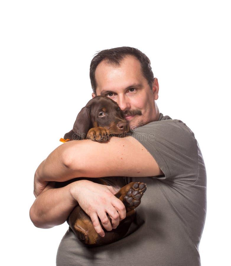 Dorosły mężczyzna trzyma jego słodkiego szczeniaka odizolowywa na białym backgroun zdjęcia stock