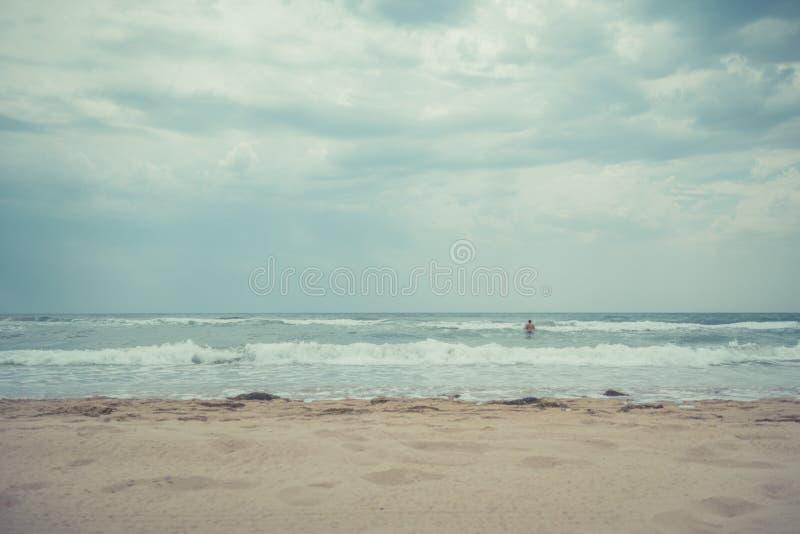 Dorosły mężczyzna w wodzie przy plażą na chmurnym dniu zdjęcia royalty free