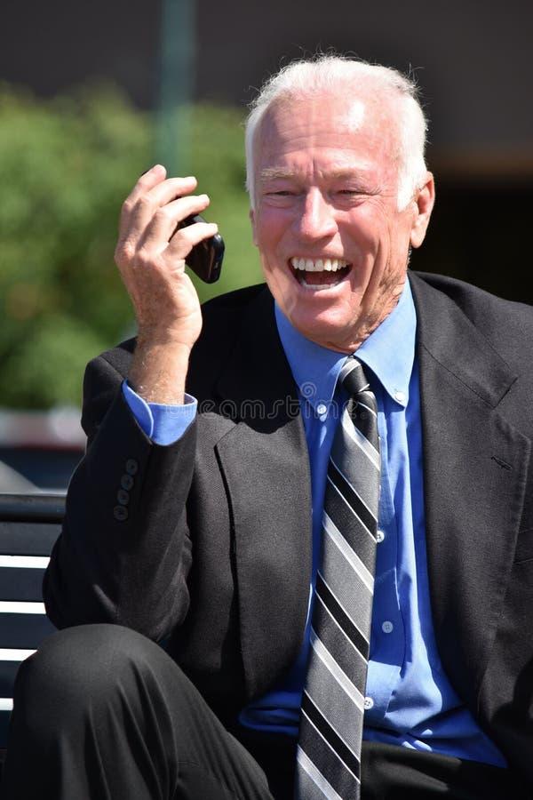 Dorosły Starszy Biznesowy mężczyzna Używa telefon komórkowego I Szczęśliwego obsiadanie obrazy royalty free