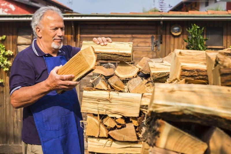 Dorosły starszy mężczyzna umieścił i sprawdził drewno, aby ogrzać dom zimą aktywność domowa na zewnątrz w okresie letnim, tani sp obraz royalty free