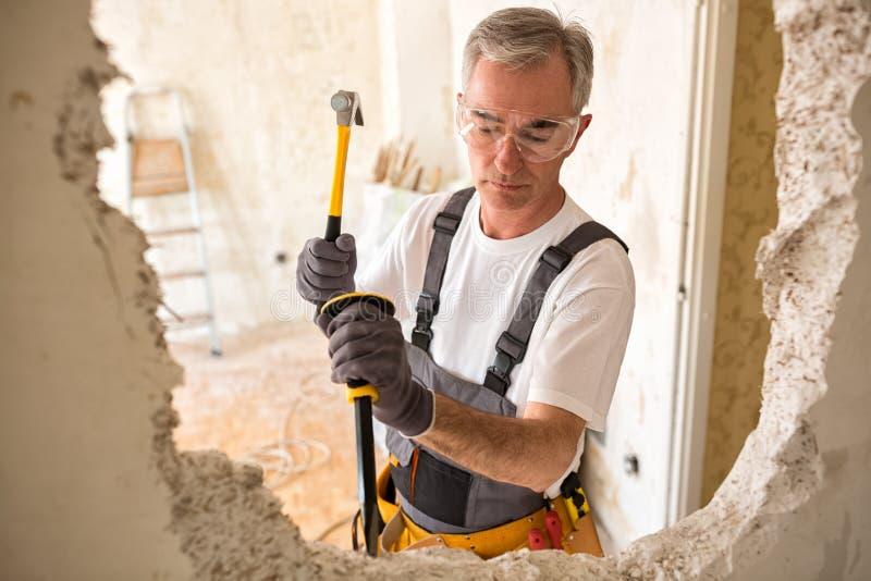Dorosły starszy pracownika budowniczy używa młot i roztrzaskania narzędzie zdjęcie stock