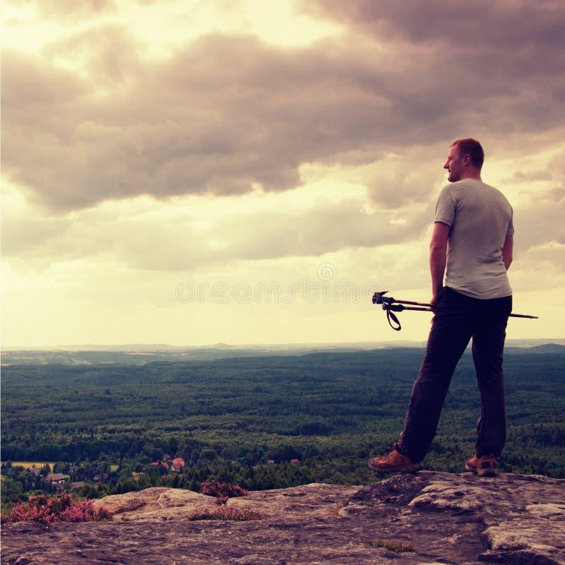 Dorosły wycieczkowicz z słupami w ręce Wycieczkowicz bierze odpoczynek na skalistym widoku punkcie nad dolina Słoneczny dzień ska fotografia stock