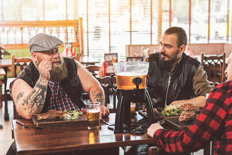 Dorosli faceci odpoczywa w pubie podczas gdy mieć gościa restauracji fotografia stock
