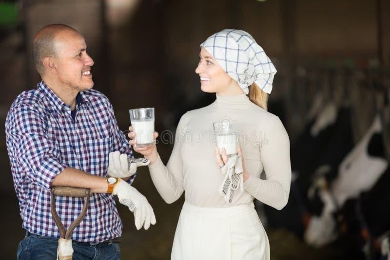 Dorosli mężczyzna i kobiety rolnicy stoi z mlekiem zdjęcie royalty free