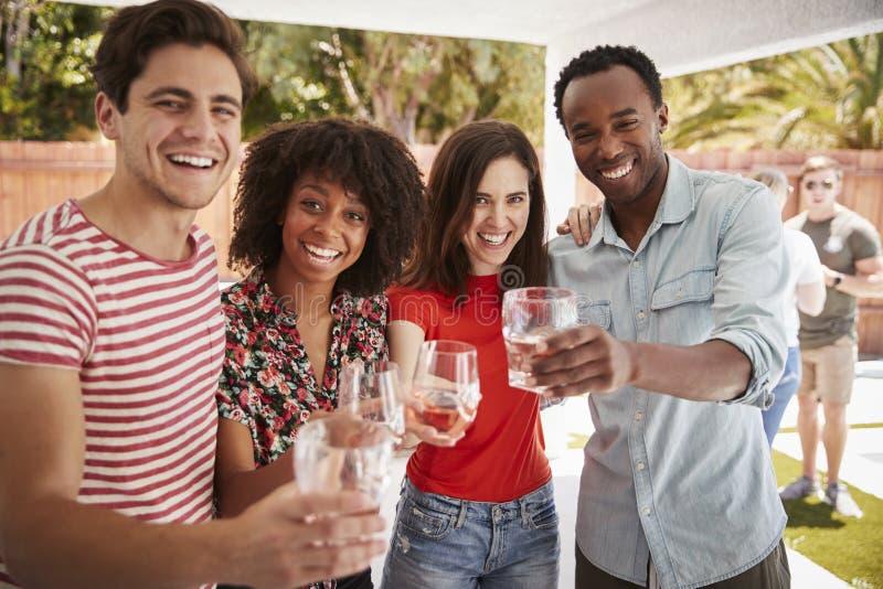 Dorosli przyjaciele przy podwórko bawją się podnoszący szkło kamera zdjęcie stock