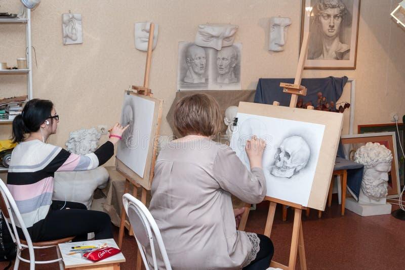Dorosli ucznie siedzą przy sztalugami, uczą się rysować zdjęcie stock