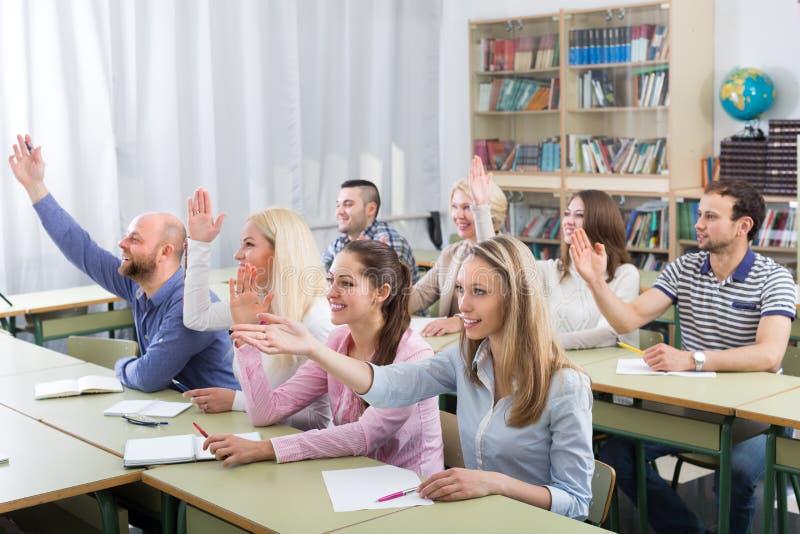 Dorosli ucznie z rękami up przy klasą obrazy stock