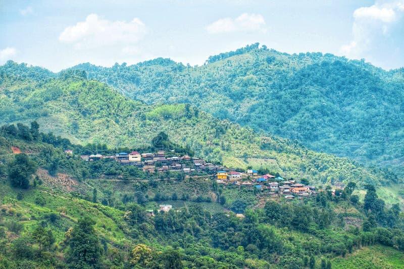 Dorp in de vallei Het leven in het bosplattelandshuisje in de berg met zonlicht Klein huis in de heuvel met blauwe hemel en c stock fotografie