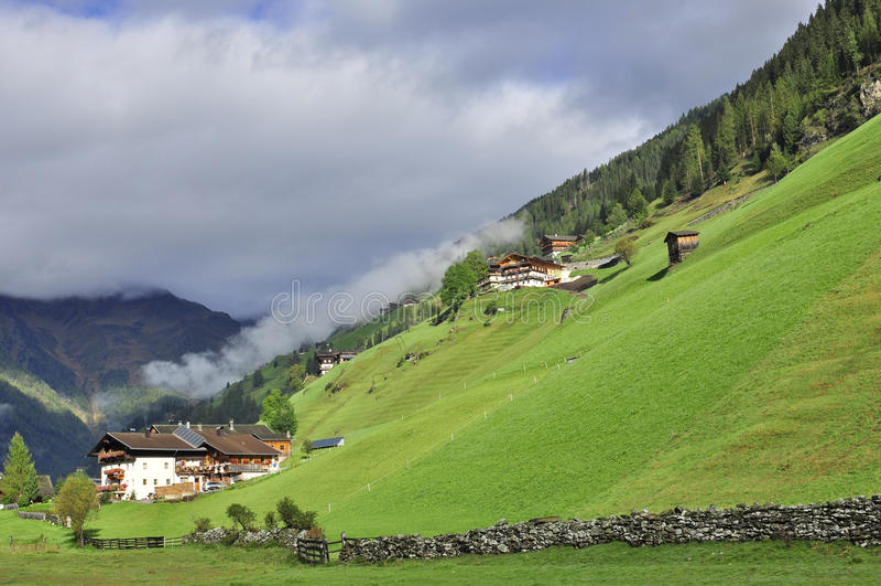Dorp in Oostenrijk met groene gazons en bergen stock foto's