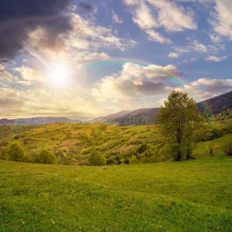 Dorp op hellingsweide in berg bij regenboogzonsondergang stock foto