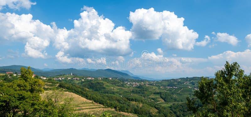 Dorp van Kojsko, beroemd die de wijnbouwgebied van Sloveniain van Goriska Brda, door zon en wolken op heilige achtergrond wordt a stock foto