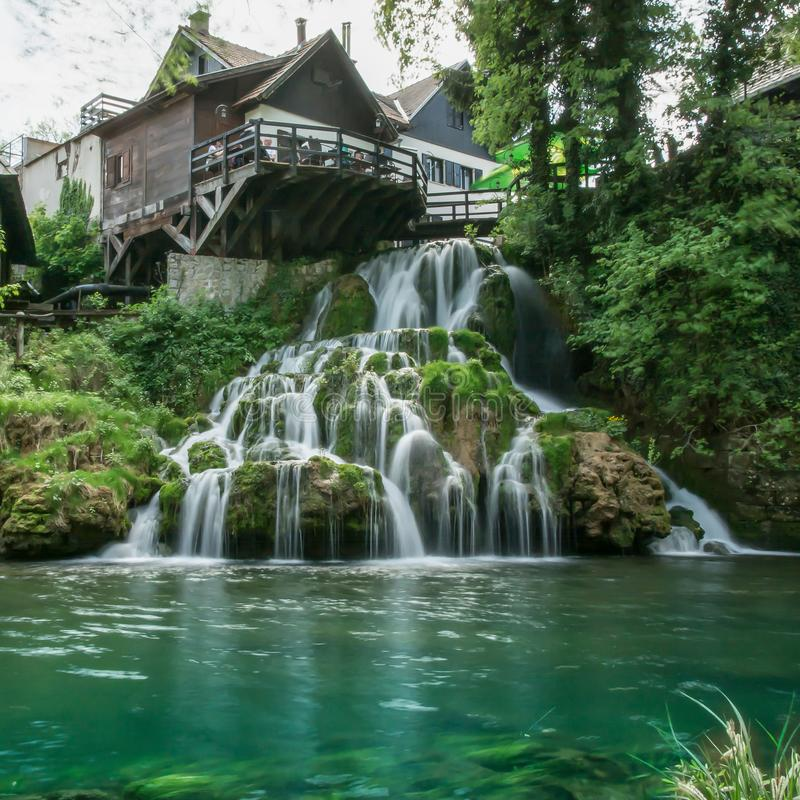 Dorp van Rastoke door een Korana-rivier met blokhuizen en een waterval, Kroatië stock foto's