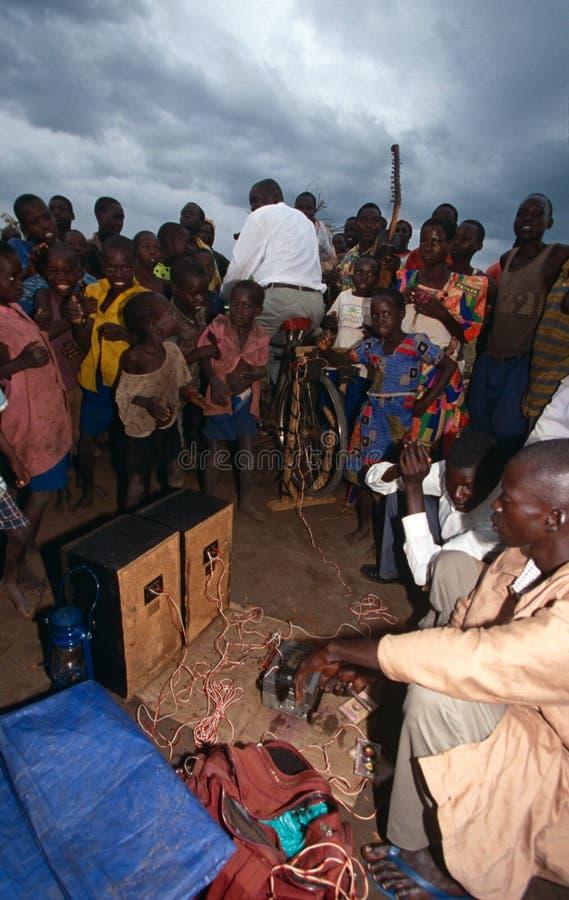 Dorpsbewoners die aan pedaal-aangedreven radio, Oeganda luisteren royalty-vrije stock foto's