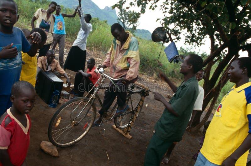 Dorpsbewoners die aan pedaal-aangedreven radio, Oeganda luisteren stock afbeelding