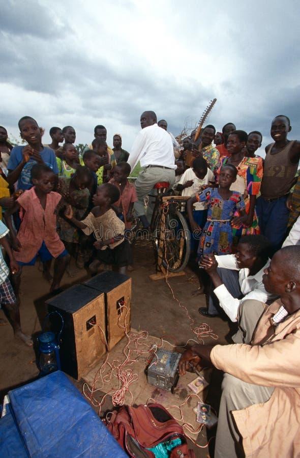 Dorpsbewoners die aan pedaal-aangedreven radio, Oeganda luisteren royalty-vrije stock fotografie