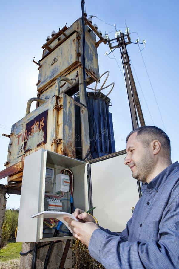Dorpsbewonertechnicus het schrijven lezing van elektriciteitsmeter op klembord stock afbeelding