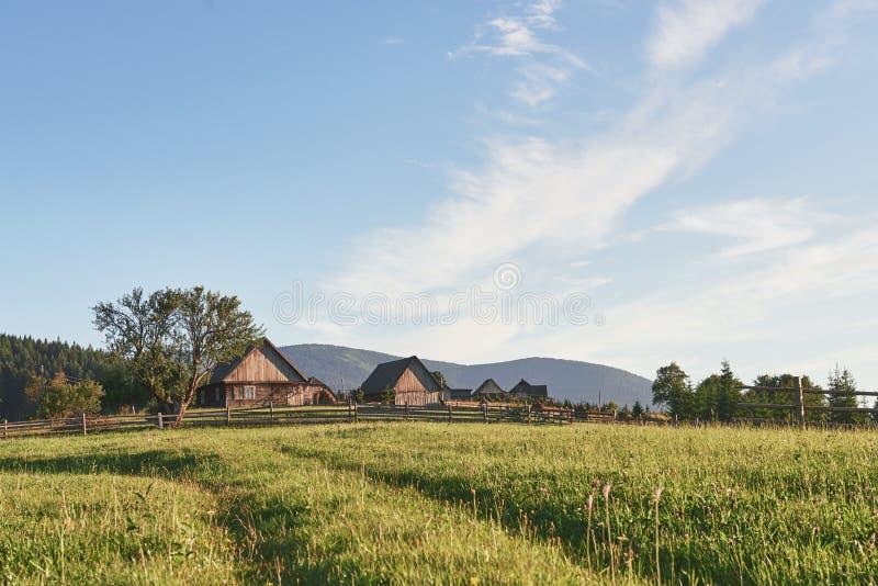 Dorpshuizen op heuvels met groene weiden in de zomerdag Huis van herders in bergen in Karpatisch stock foto's