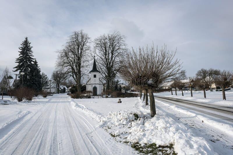 Dorpskerk in het midden van een sneeuw romantisch dorp in de winter royalty-vrije stock foto